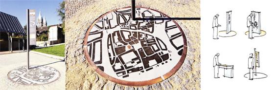 Centre historique de Naumburg - Meusen architectes GmbH. Ce projet se compose un plan schématique du centre historique au sol et d'un potelet d'indication. Il propose un dispositif de signalétique ludique qui permet à l'usager de se repérer rapidement grâce à l'emplacement du potelet sur le plan situé au sol.