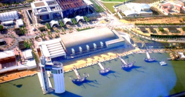 "Fig. 3. Navigation Pavilion: aerial view during Expo'92 showing its riverside orientation, curved shipping ""warehouse"" form, viewing tower and ships moored for the event.3"