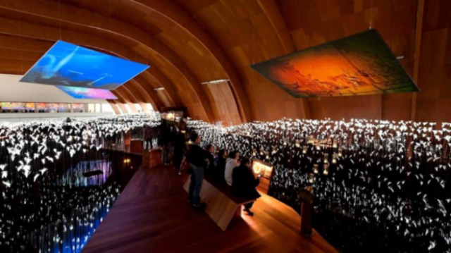 Fig. 5. Navigation Pavilion post transformation: view of new exhibition Area 1 — Sea of Souls — showing the hull-like interior space, timber deck through the LED light sea, interactive settings and overhead projection screens.