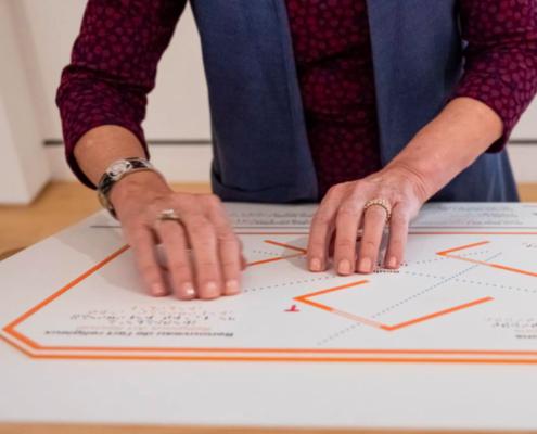 Une visiteuse teste l'un des plans d'orientation tactile du MNBAQ
